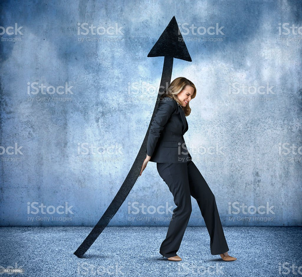 Businesswoman Supporting Upward Pointing Arrow On Her Back stock photo