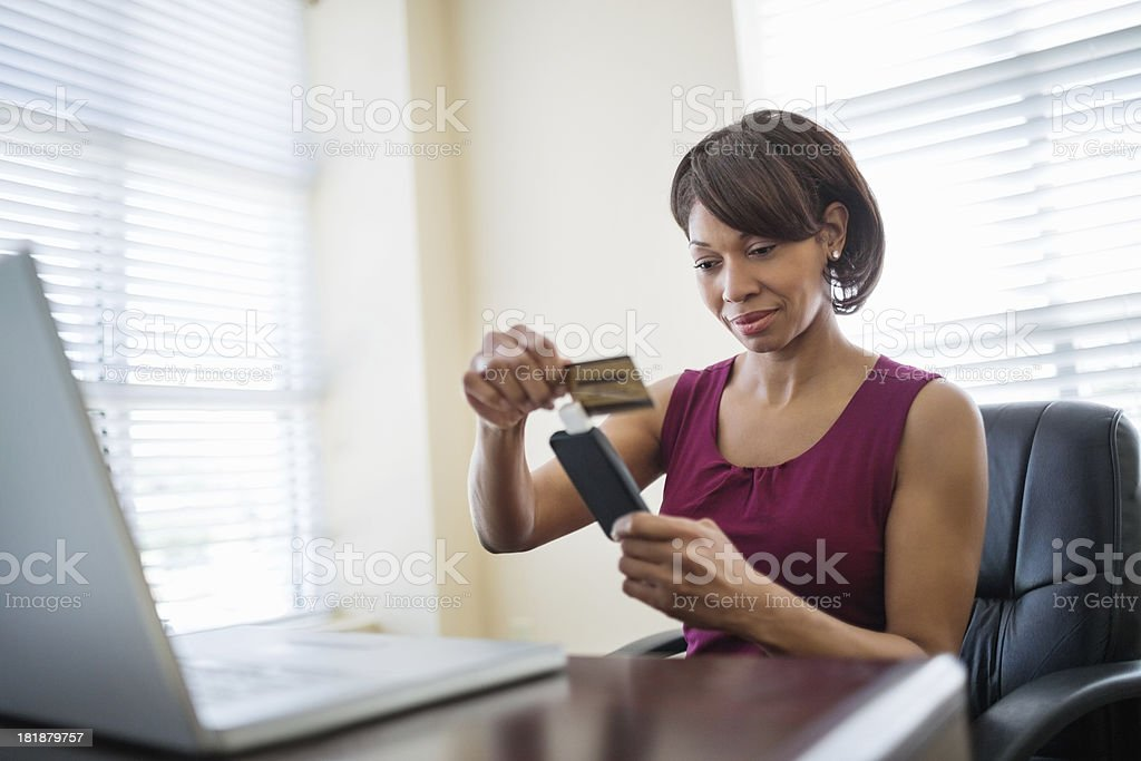 Businesswoman Swiping Credit Card Using Reader stock photo