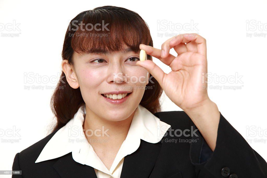 businesswoman takes a supplement stock photo