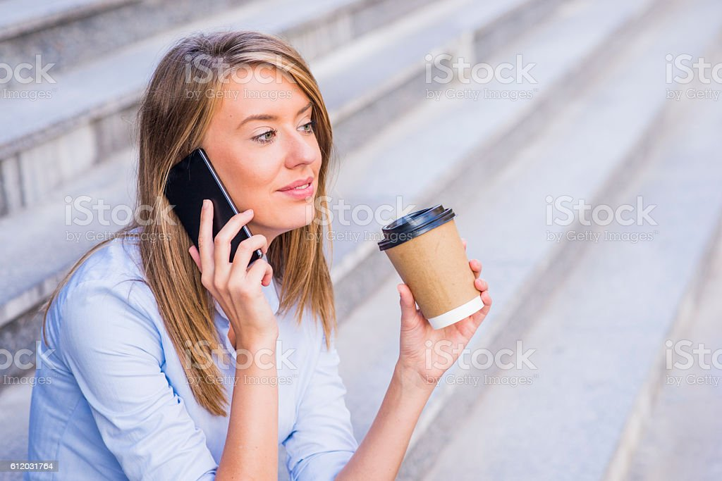Businesswoman taking a coffee break and using smartphone. stock photo