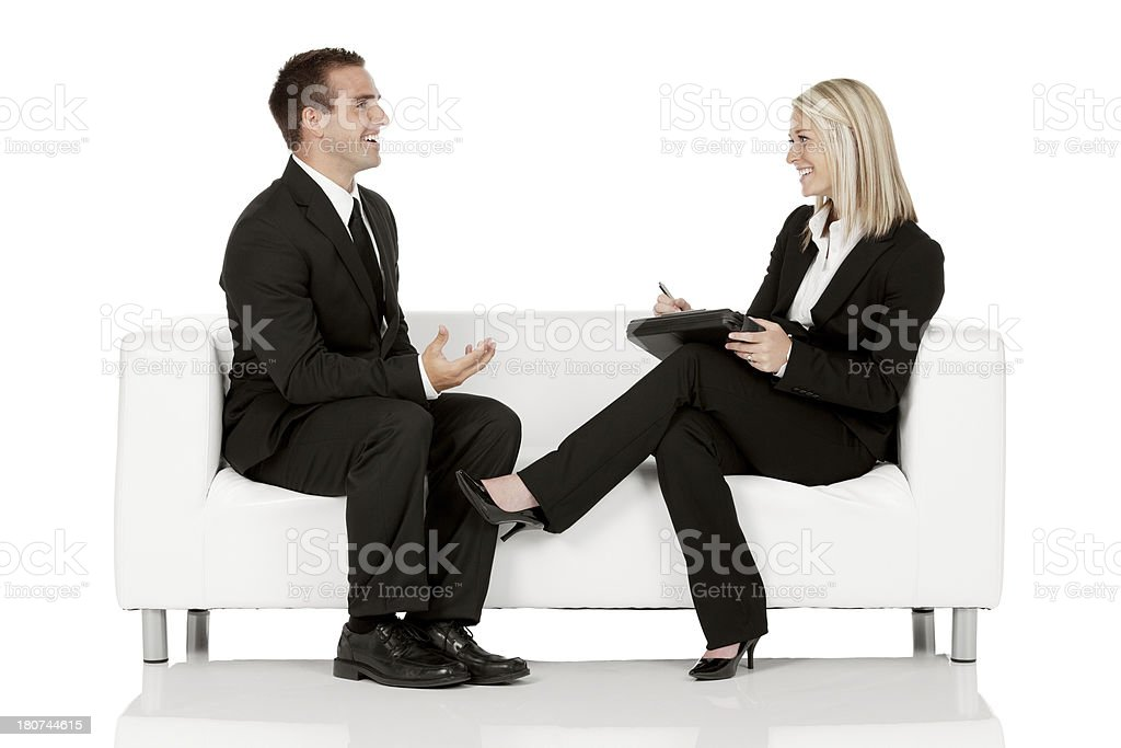 Businesswoman taking interview of a businessman stock photo