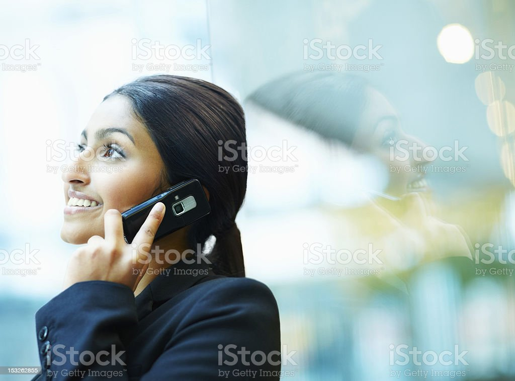 Businesswoman taking on cellphone and smiling royalty-free stock photo