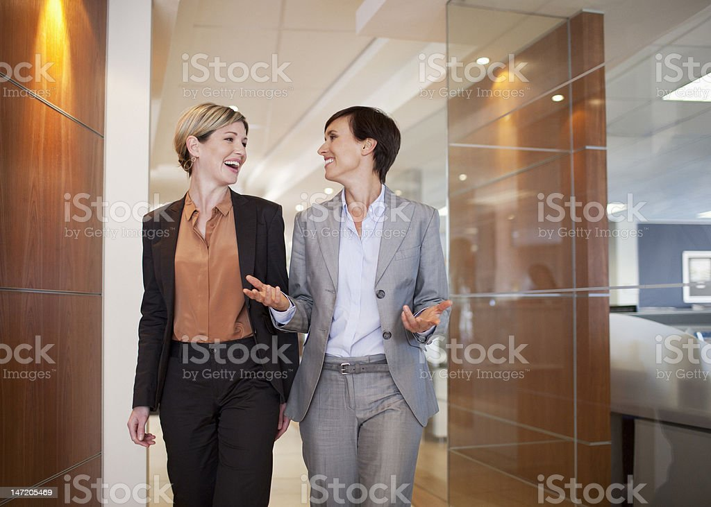 Businesswoman talking and walking in office corridor royalty-free stock photo