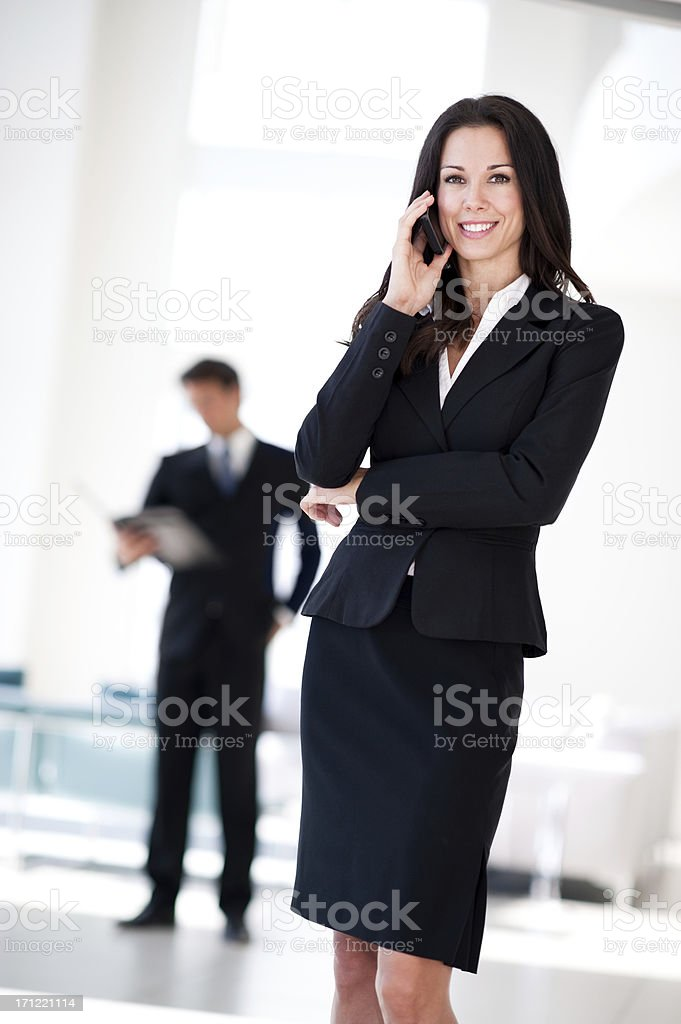 Businesswoman Talking on Cell Phone and Businessman in Lobby royalty-free stock photo