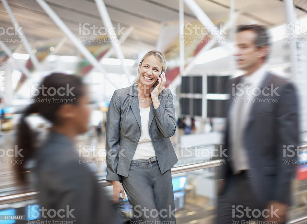 Businesswoman talking on cell phone in airport stock photo