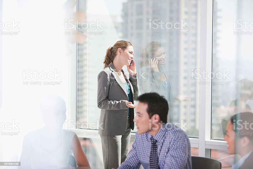 Businesswoman talking on cell phone in meeting stock photo
