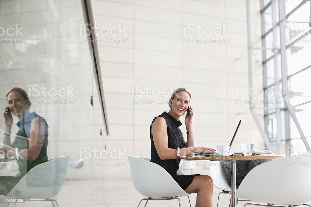 Businesswoman talking on cell phone while sitting in cafeteria royalty-free stock photo