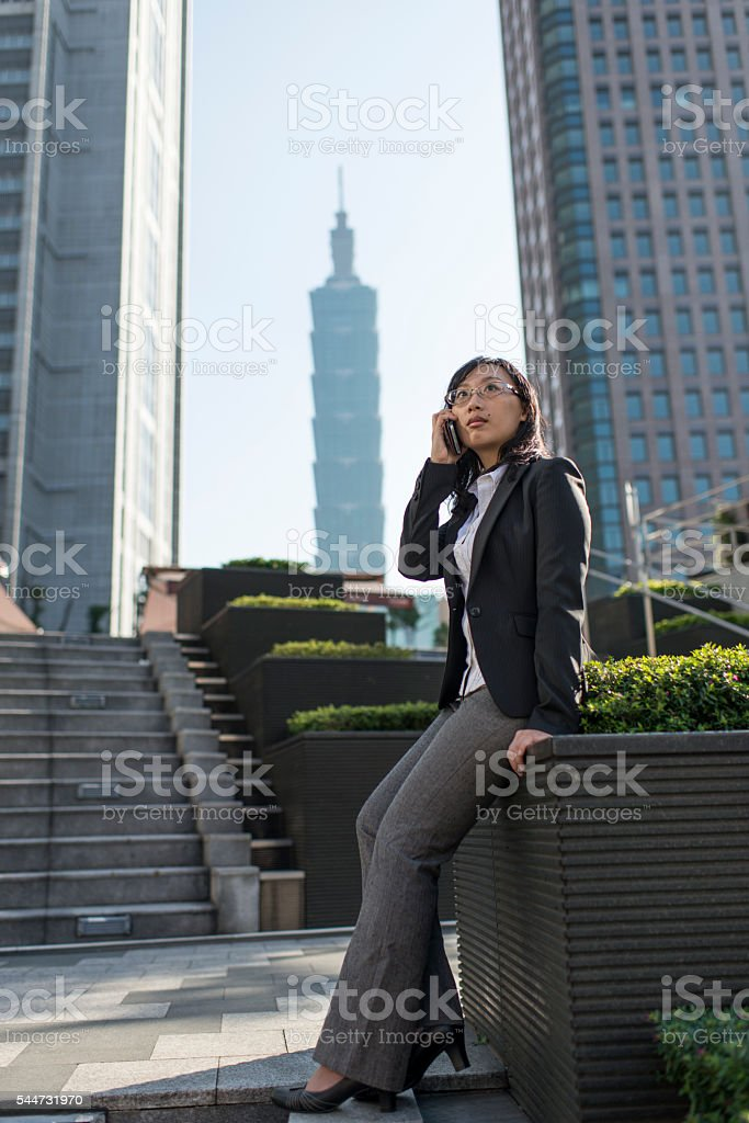 Businesswoman talking on mobile phone in city. stock photo