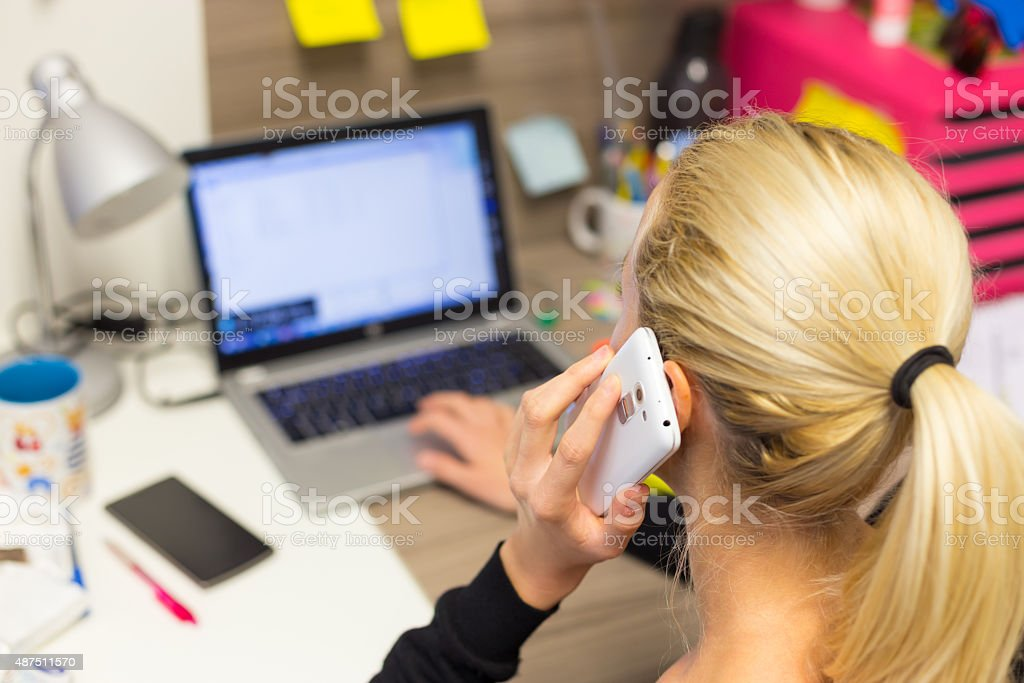 Businesswoman talking on mobile phone in office. stock photo