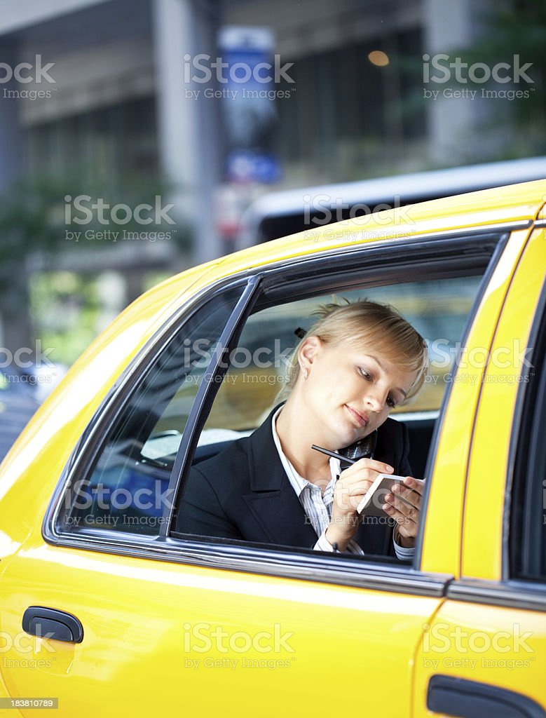 Businesswoman talking on phone and writing notes yellow cab taxi stock photo