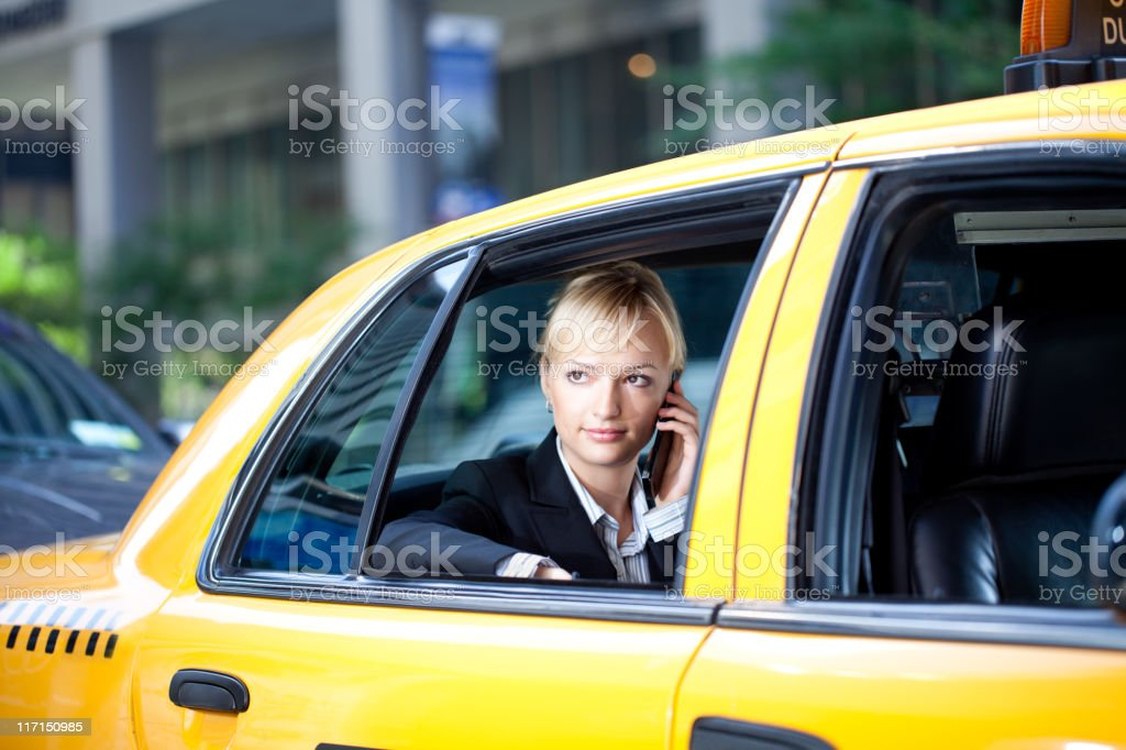 Businesswoman talking on phone in yellow cab taxi stock photo