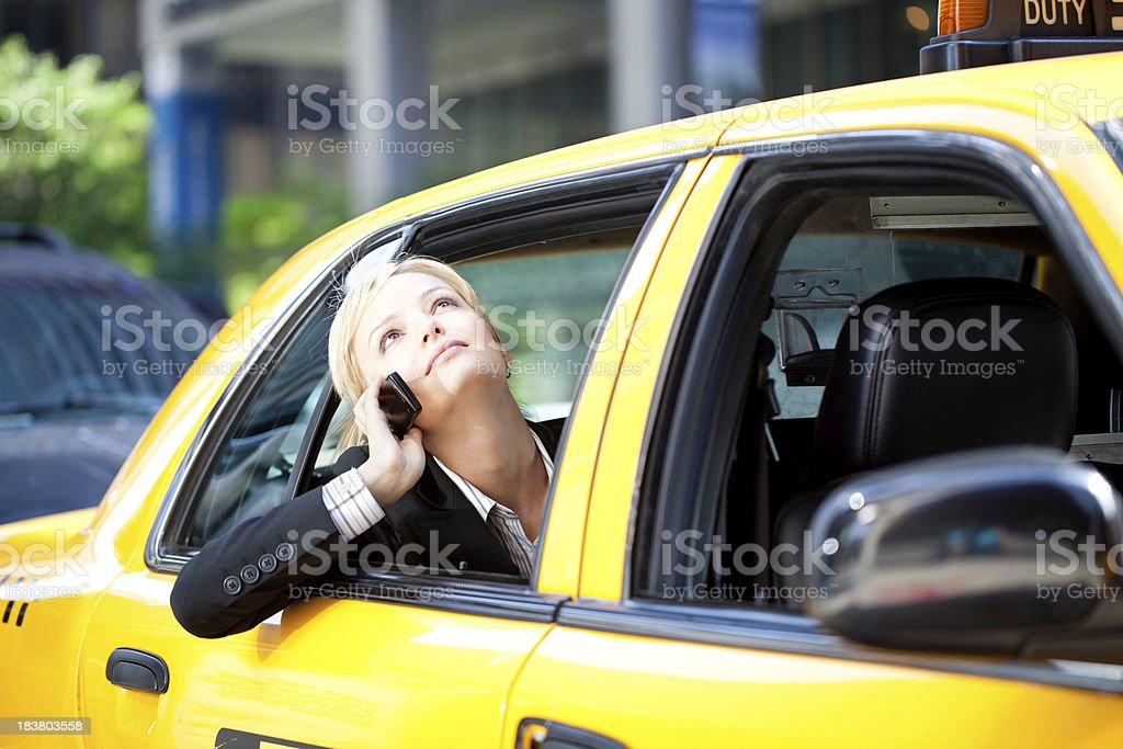 Businesswoman talking on phone in yellow cab taxi royalty-free stock photo