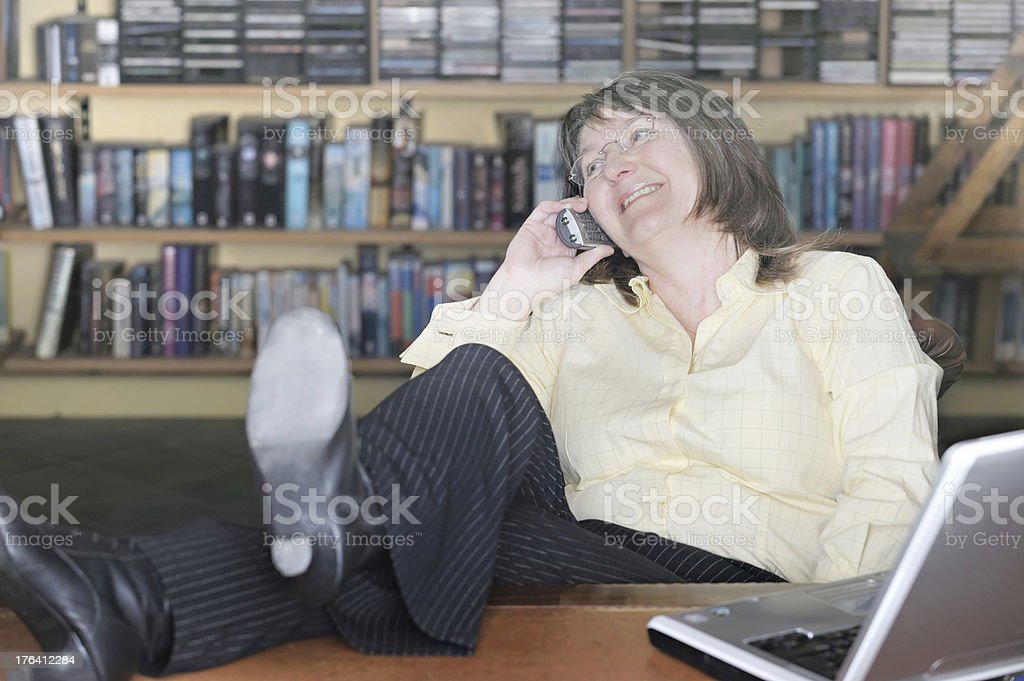Businesswoman talking on phone relaxed with feet up royalty-free stock photo