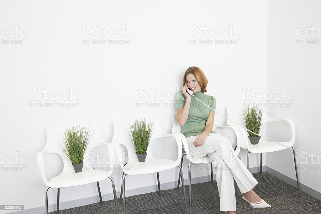Businesswoman talking on phone surrounded by plants stock photo