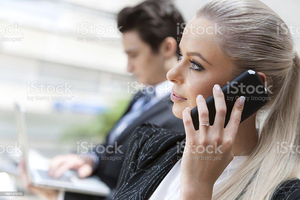 Femme d'affaires sur le téléphone intelligent de réunion photo libre de droits