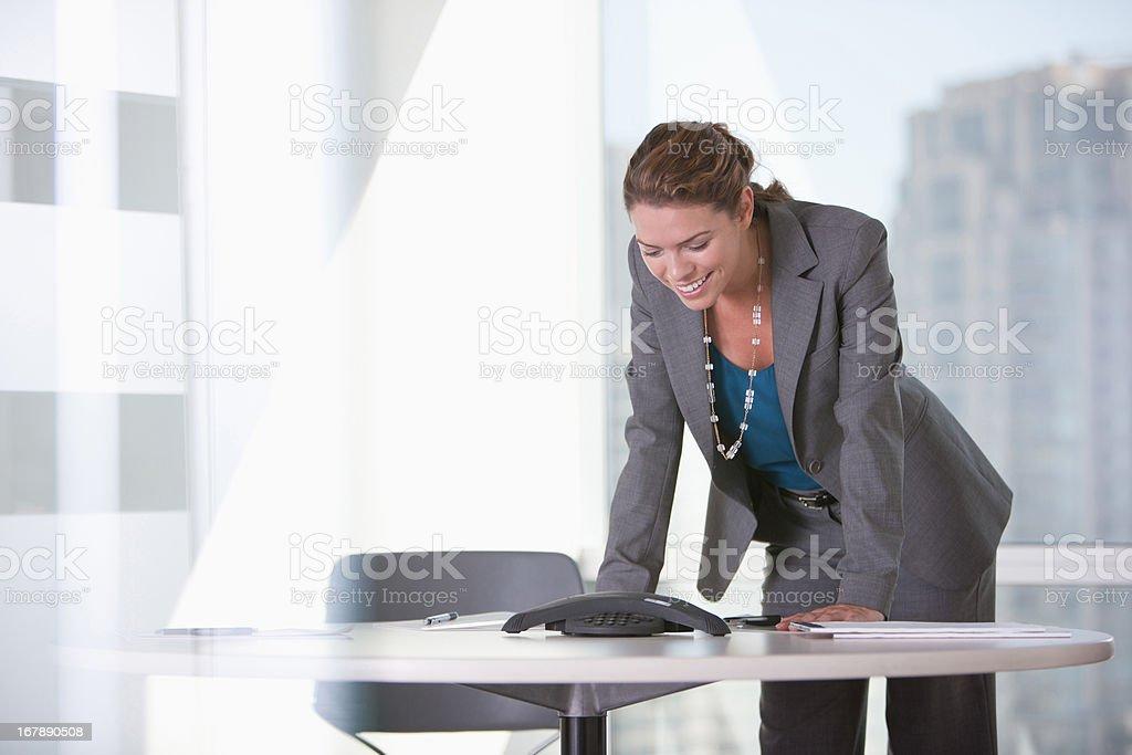 Businesswoman talking on speaker phone stock photo