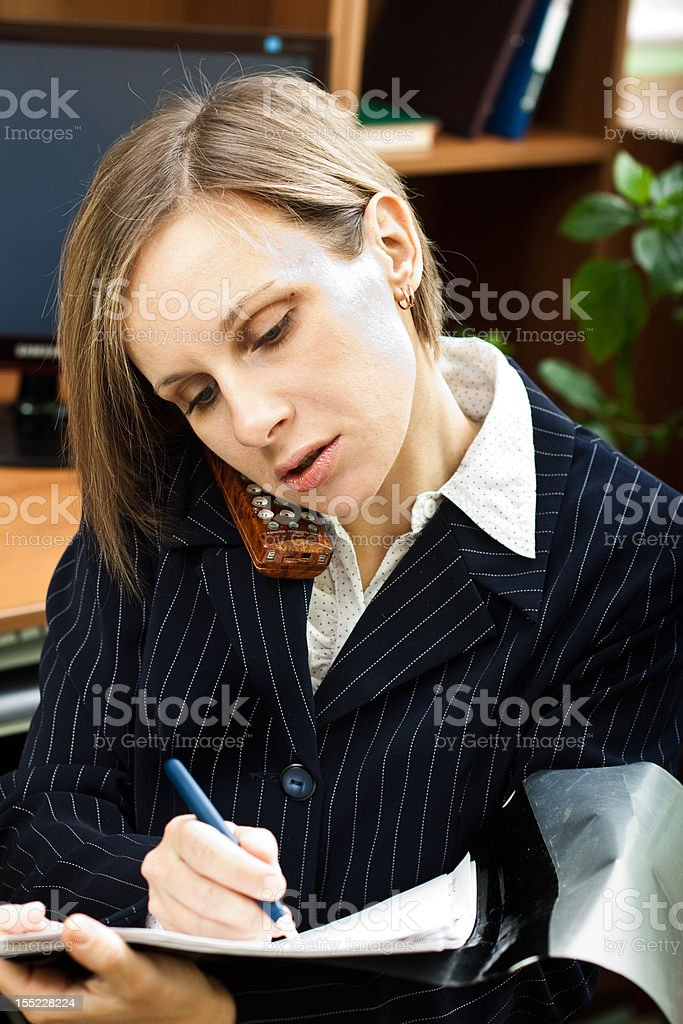 Businesswoman talking on the phone and writes royalty-free stock photo