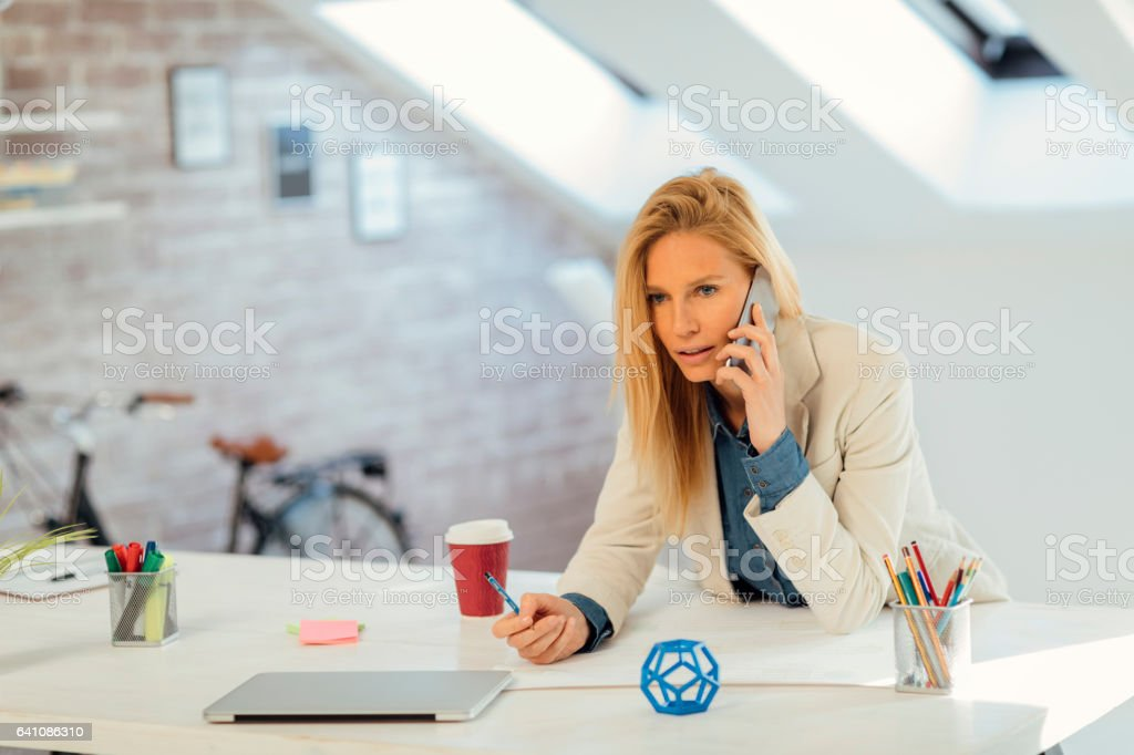 Businesswoman talking on the phone in her office stock photo