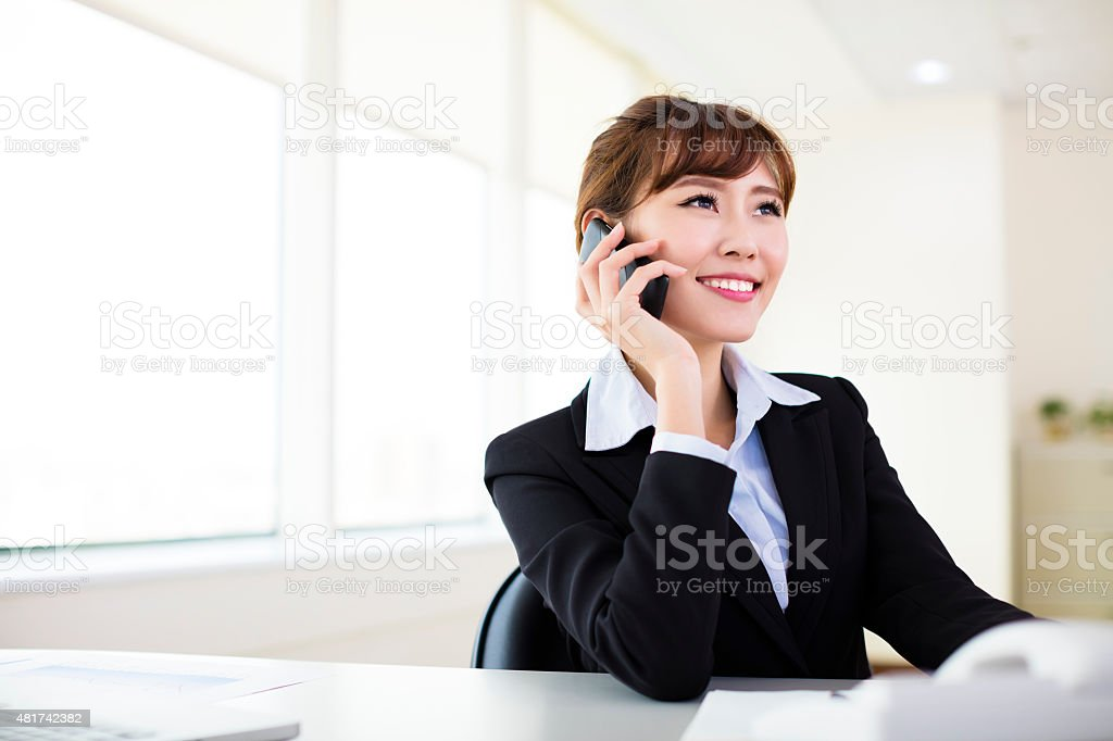 businesswoman talking on the phone in the office stock photo