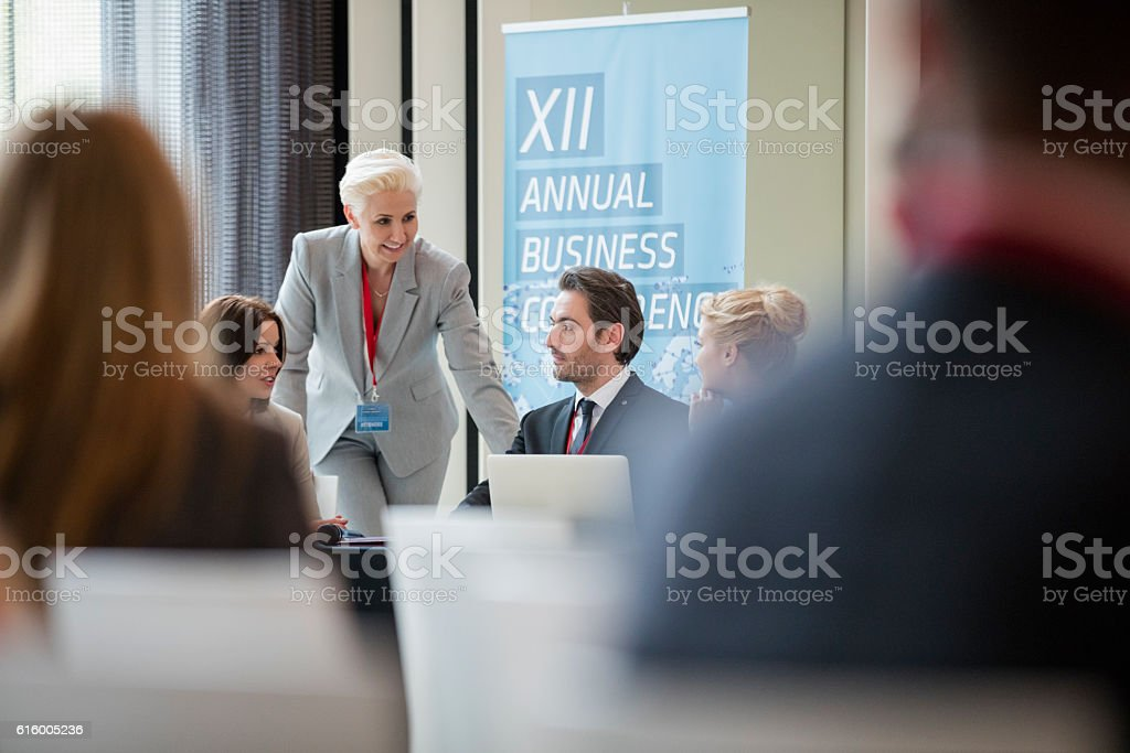Businesswoman talking to colleagues during seminar stock photo