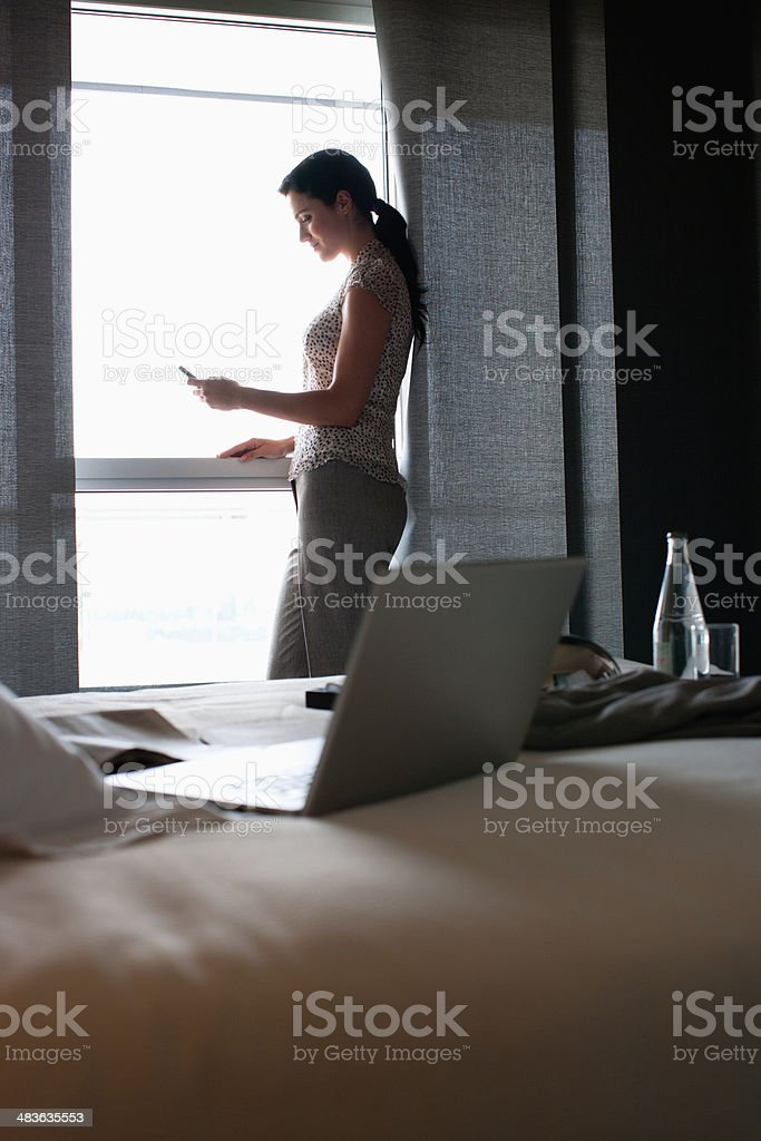 Businesswoman text messaging in hotel room stock photo