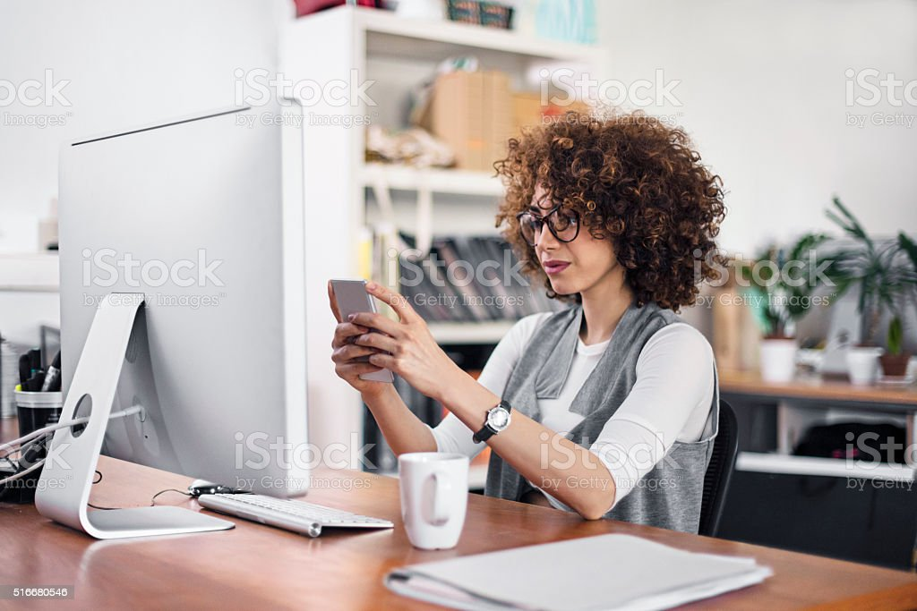Businesswoman texting a message in the mobile phone at office stock photo