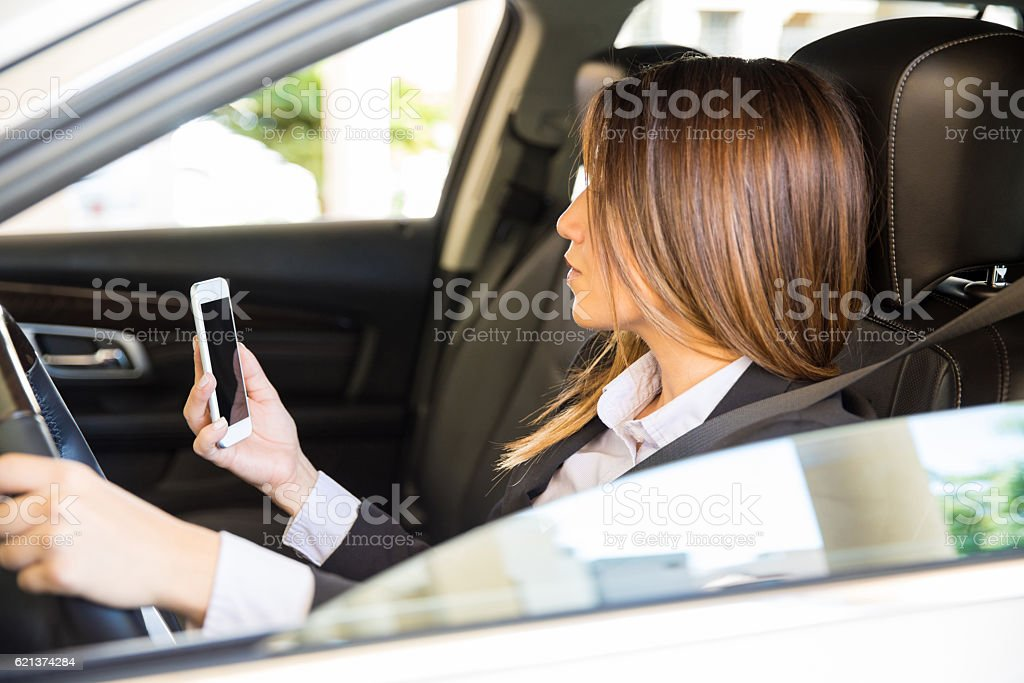 Businesswoman texting and driving stock photo