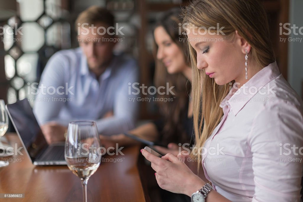 Businesswoman texting during lunch break stock photo
