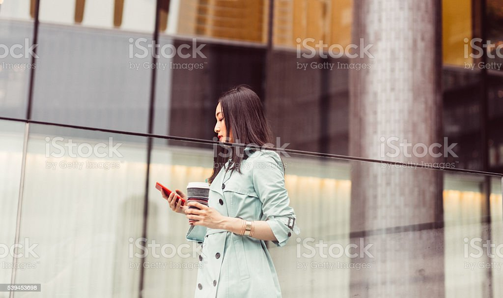 Businesswoman texting in the office stock photo