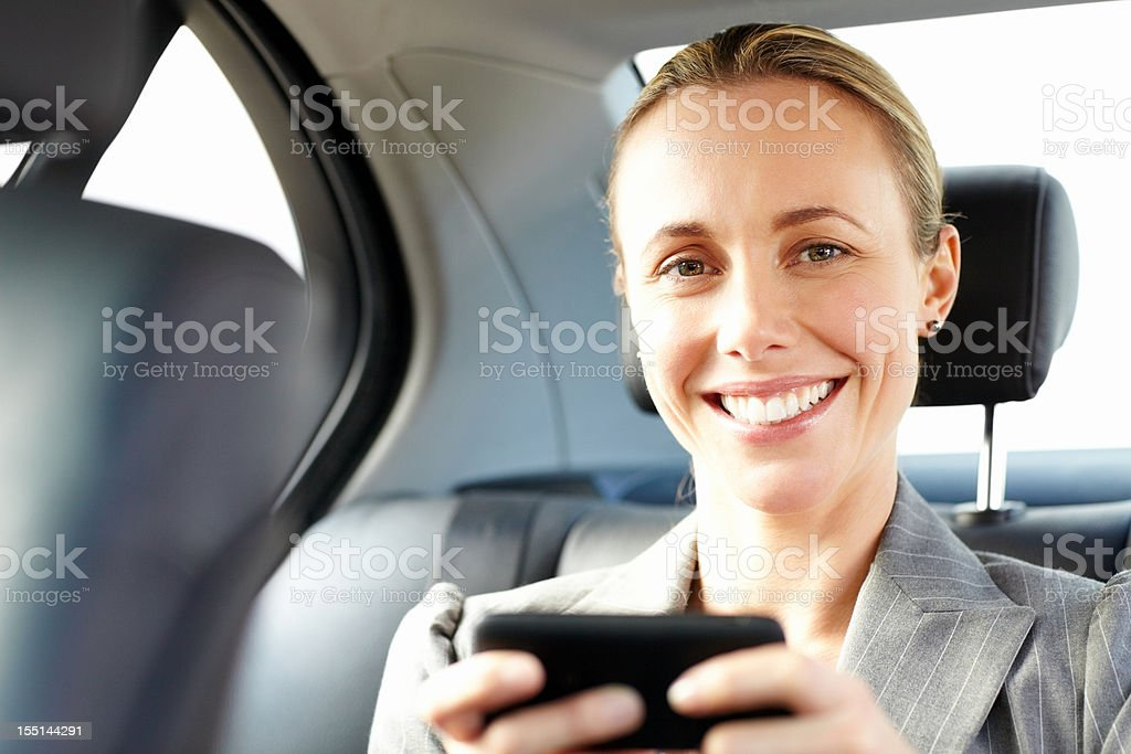 Businesswoman Texting on a Cellphone in the Car royalty-free stock photo