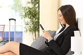 Businesswoman texting on phone in an hotel