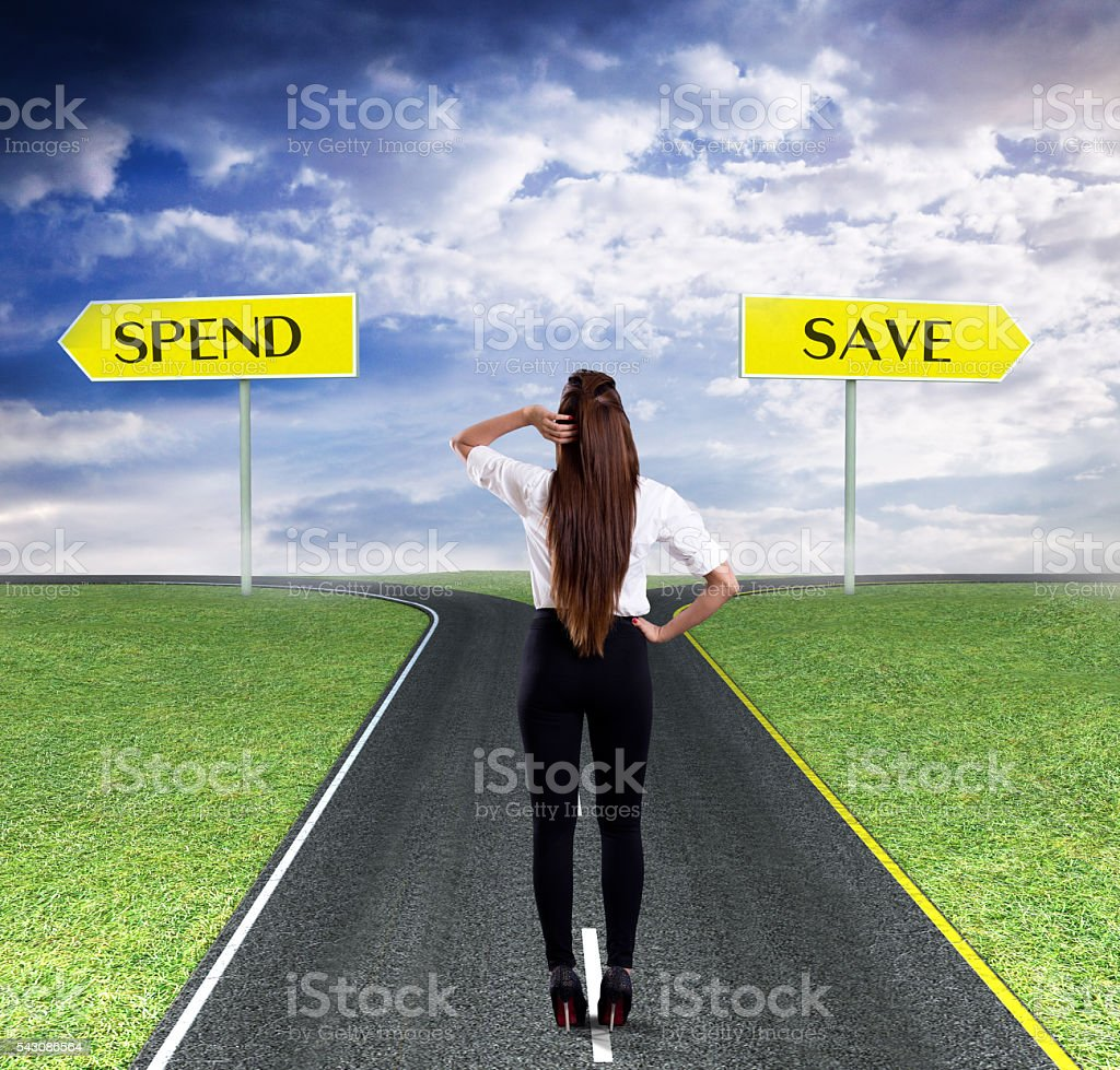 Businesswoman thinking about spend or save stock photo