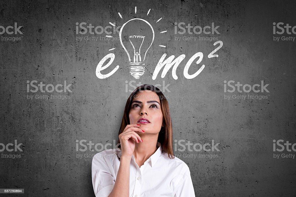 Businesswoman thinking of Albert Einstein formula stock photo