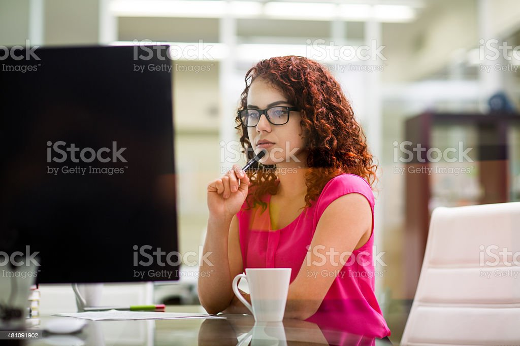 Businesswoman thinking while working at office stock photo