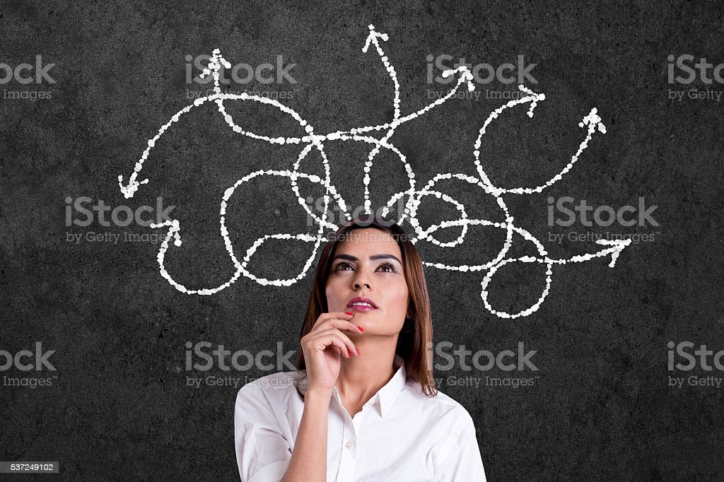 Businesswoman thinking with arrows coming from her head stock photo