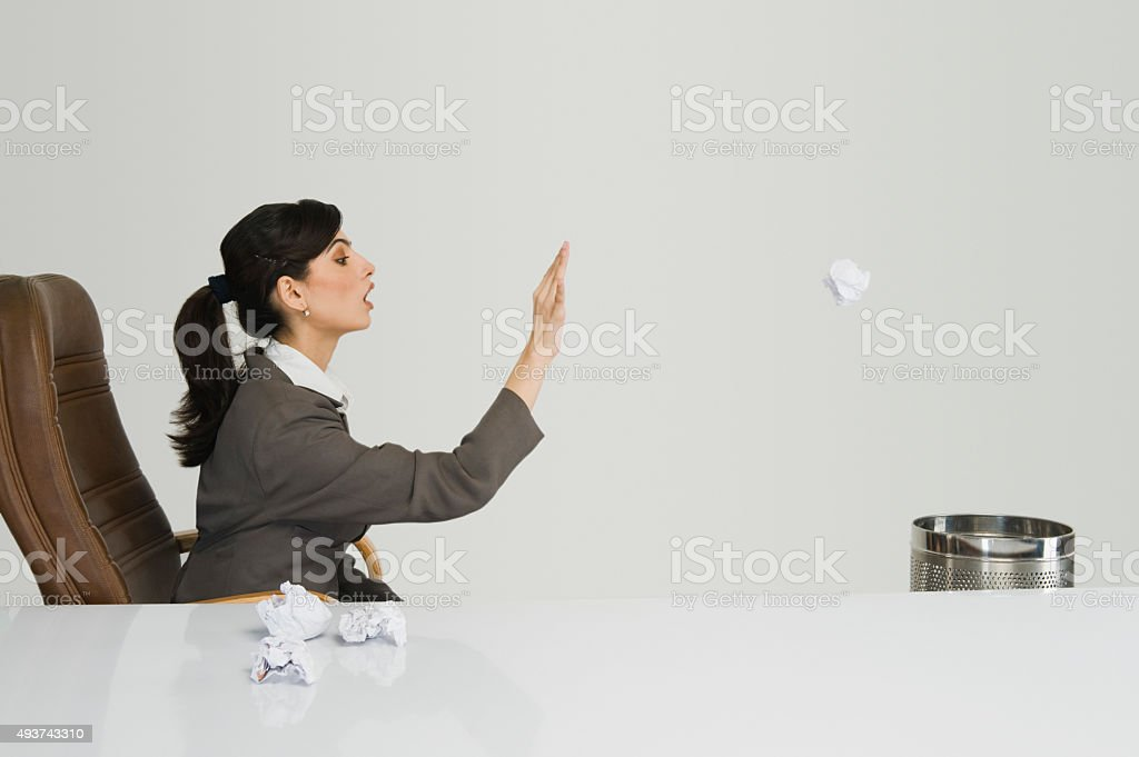 Businesswoman throwing crumpled paper into a wastepaper basket stock photo