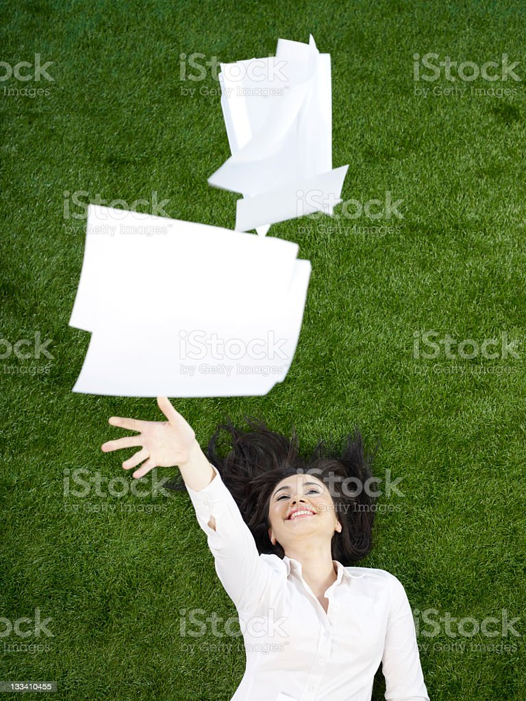 Businesswoman throwing papers in air royalty-free stock photo