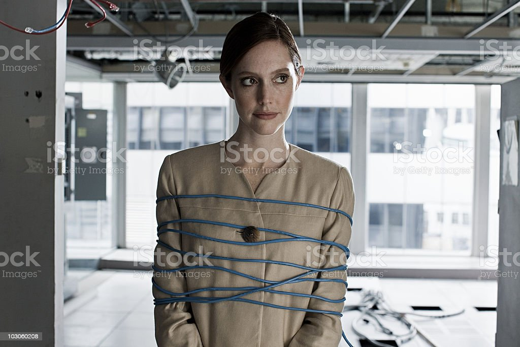 Businesswoman tied up in cables stock photo