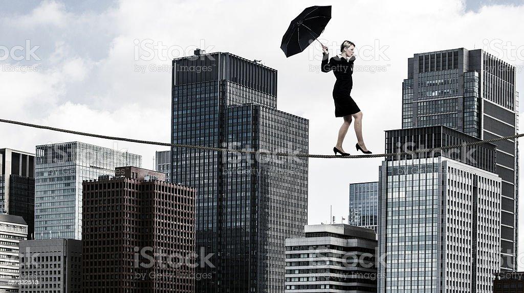 Businesswoman tightrope walker stock photo