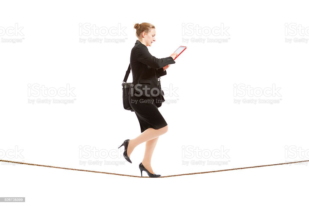 Businesswoman Tightrope Walker Using Digital Tablet Computer on White Background stock photo