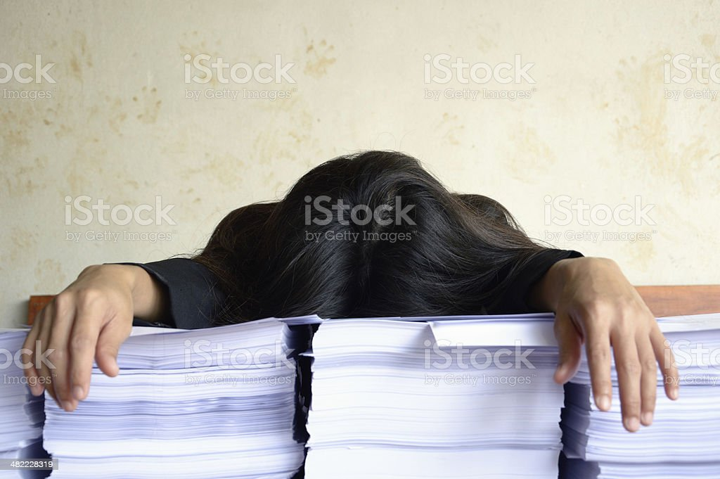 businesswoman tired and sleep at pile of papers stock photo
