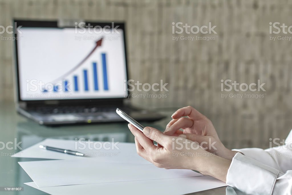 Businesswoman touching smartphone touchscreen stock photo