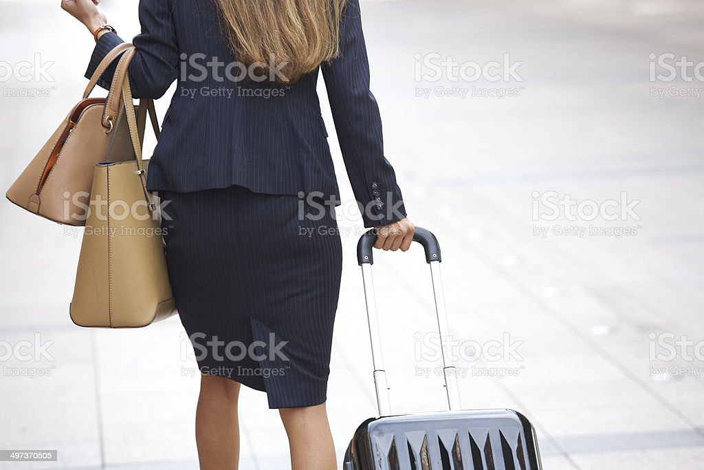 Businesswoman traveling with luggage and handbags stock photo