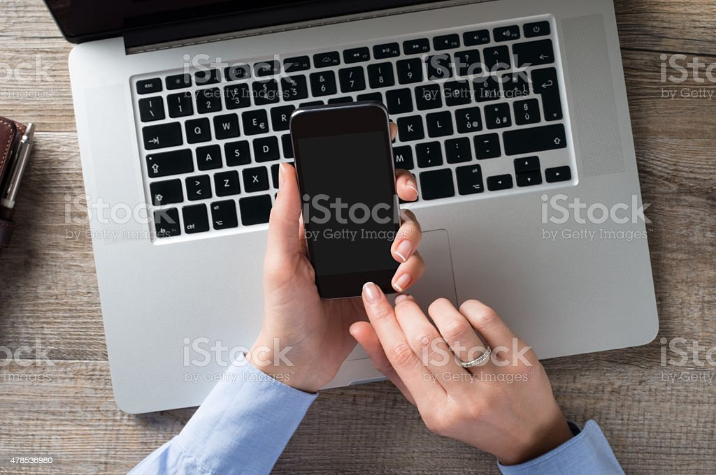 Businesswoman typing a text on mobile phone stock photo