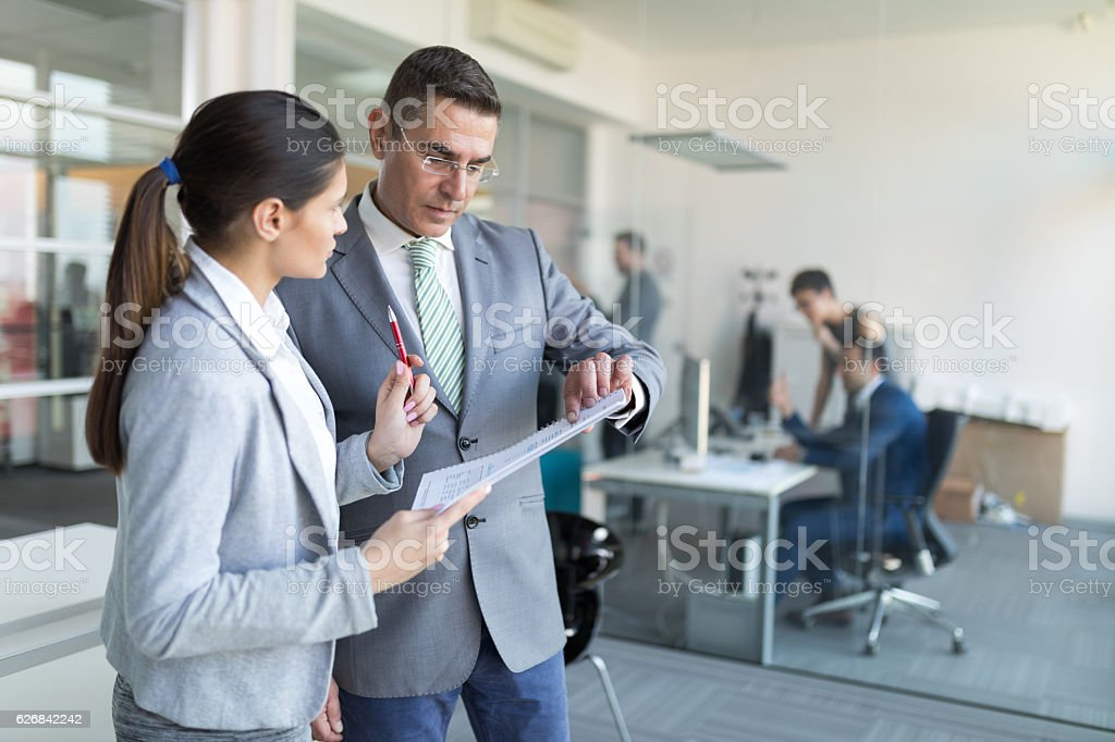 Businesswoman updating senior colleague on business project progress stock photo