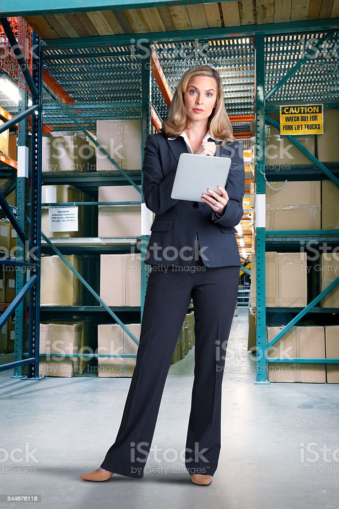 Businesswoman Using A Digital Tablet In A Warehouse stock photo