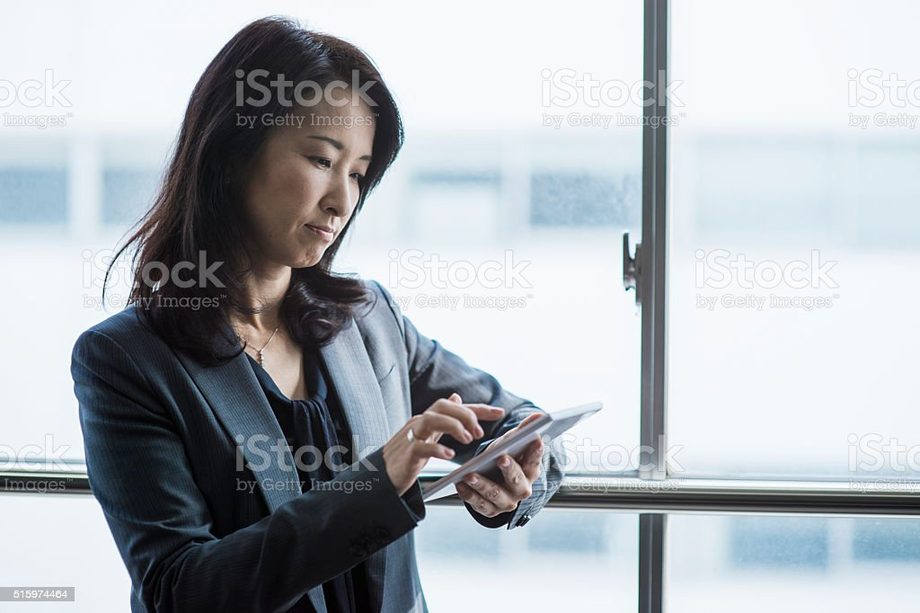 Businesswoman using a digital tablet in office stock photo