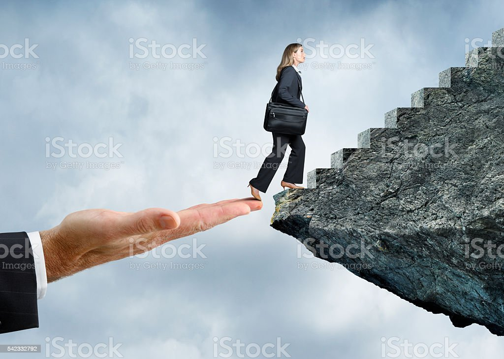 Businesswoman Using A Helping Hand To Reach Her Goal stock photo
