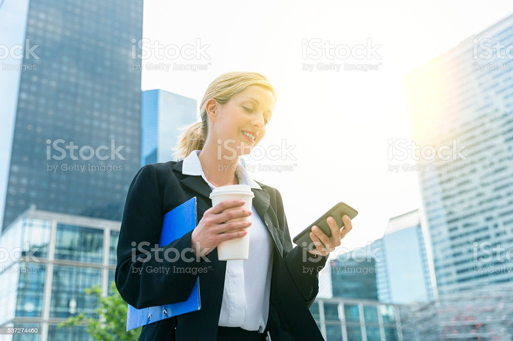 Businesswoman using a smartphone in financial district stock photo