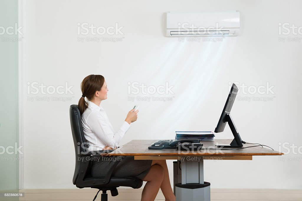 Businesswoman Using Air Conditioner In Office stock photo